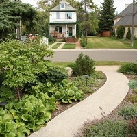 Front yard landscaping for a mature lot using a garden design plan that includes beautiful flower garden ideas.